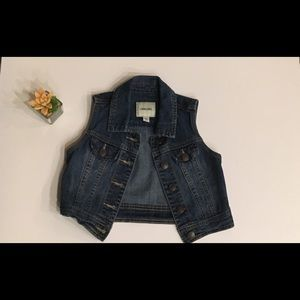 A cropped sleeveless jean jacket